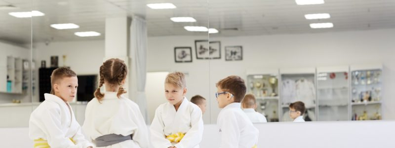 Group of children in kimono sitting on the floor and talking to each other during their lesson in karate in the gym